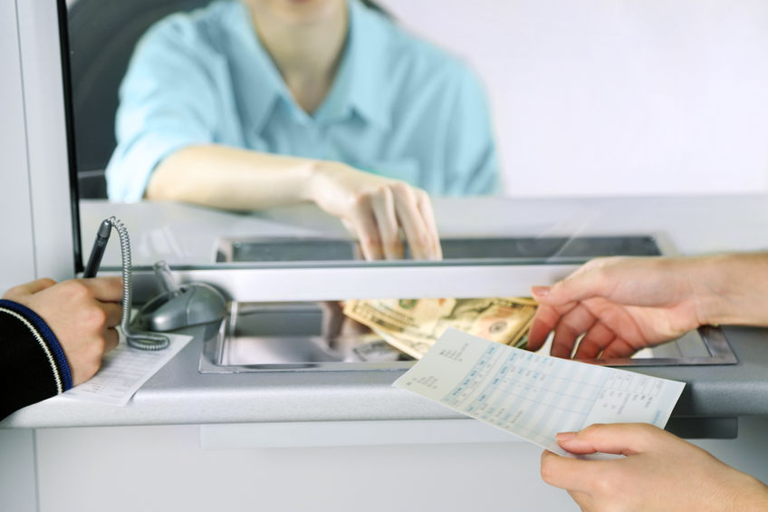 Quick Loans Direct shares photo of bank teller for small business lending.
